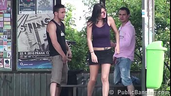A guy is sharing a girlfriend with his friend at a bus stop