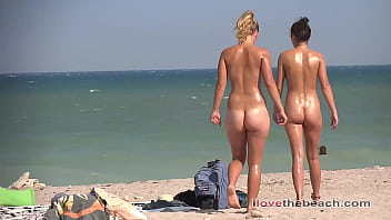 Blonde and brunette bathing and sunbathing naked on the beach.