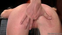 Busty redhead is spanked with plank